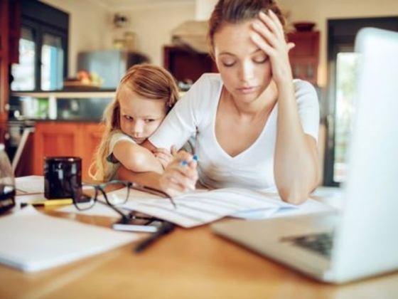 madre intentando leer un documento con su niña colgada del brazo