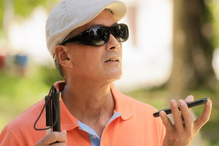 hombre con ceguera escuchando el celular