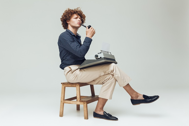 hombre sentado con una máquina de escribir y una pipa