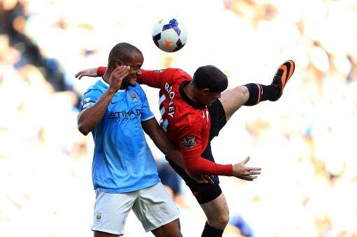 Wayne Rooney and Vincent Kompany Goes for an Aerial Header.