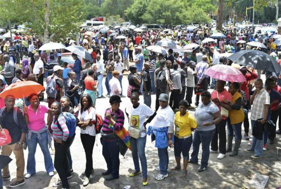 People wait for transport to take them to view the body of former South African President Nelson Mandela, at the Union Buildings in Pretoria