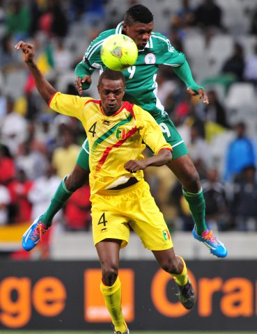 Gbolahan Salami Challenges for an Aeriel Ball Against a Malian Opponent During a 2014 CHAN Group Game.