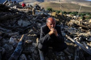 A victim of earthquake sits on the ruins of buildings at the village of Bajebaj near the city of Varzaqan in northwestern Iran, Sunday, Aug. 12, 2012