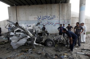 Residents gather at the site of a bomb attack in Baghdad's Hussainiya
