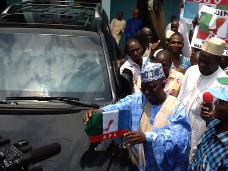 GOV. AL-MAKURA HOISTING THE APC FLAG ON HIS OFFICIAL VEHICLE ON SATURDAY