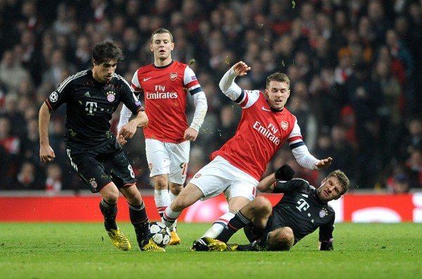 Thomas Muller Tackles Arsenal's Lukas Podolski in a Round of 16 Tie at the Emirate Stadium.Getty Image.