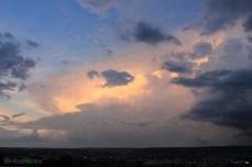 Vers le nord-ouest, un ciel dégagé laisse apparaître le sommet du cumulonimbus imposant, lors du couché de soleil.