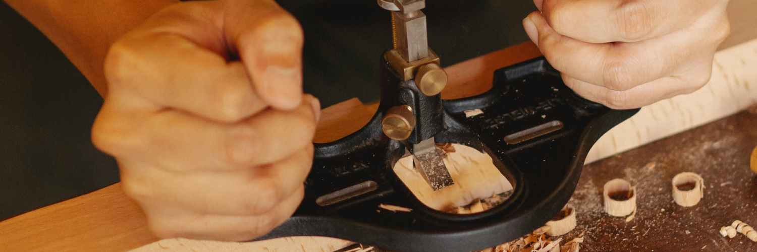 close up photo of craftsman crafting wooden plank