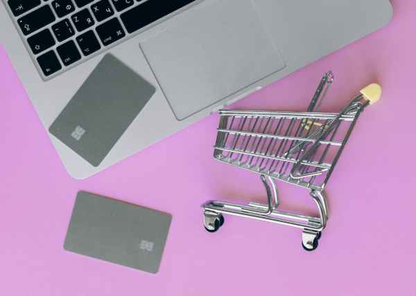 silver shopping cart on pink surface