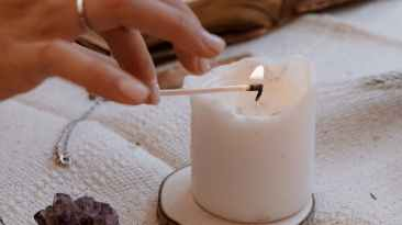 person holding white candle with white candle