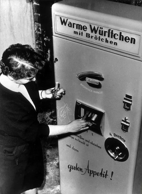 Germany, Berlin: Vending machine selling hot sausages presentet on the industries fair. 1954