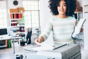 Female assistant using copy machine at workplace