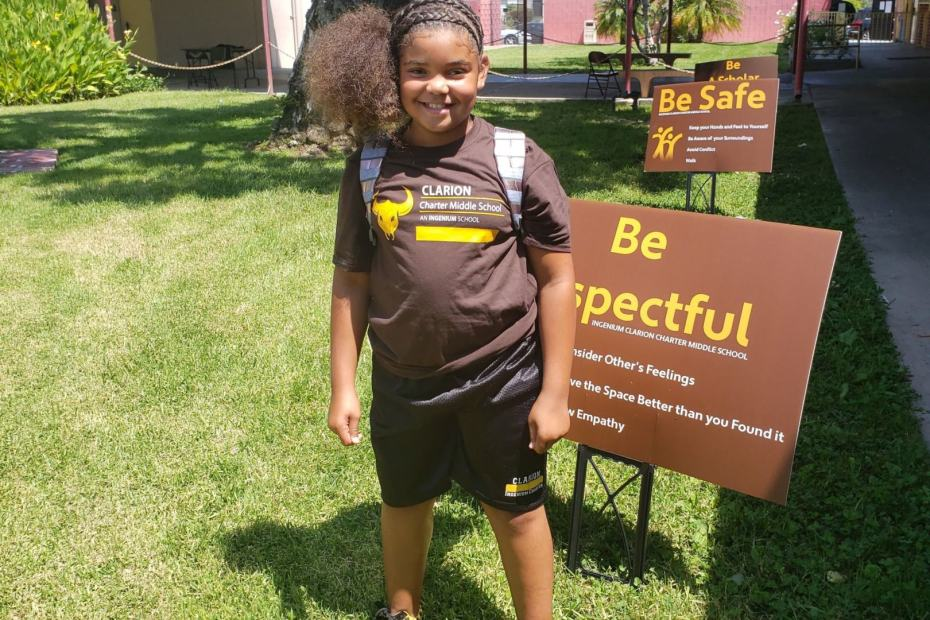 "ICCMS student standing in front of a ""Be Respectful"" Sign"