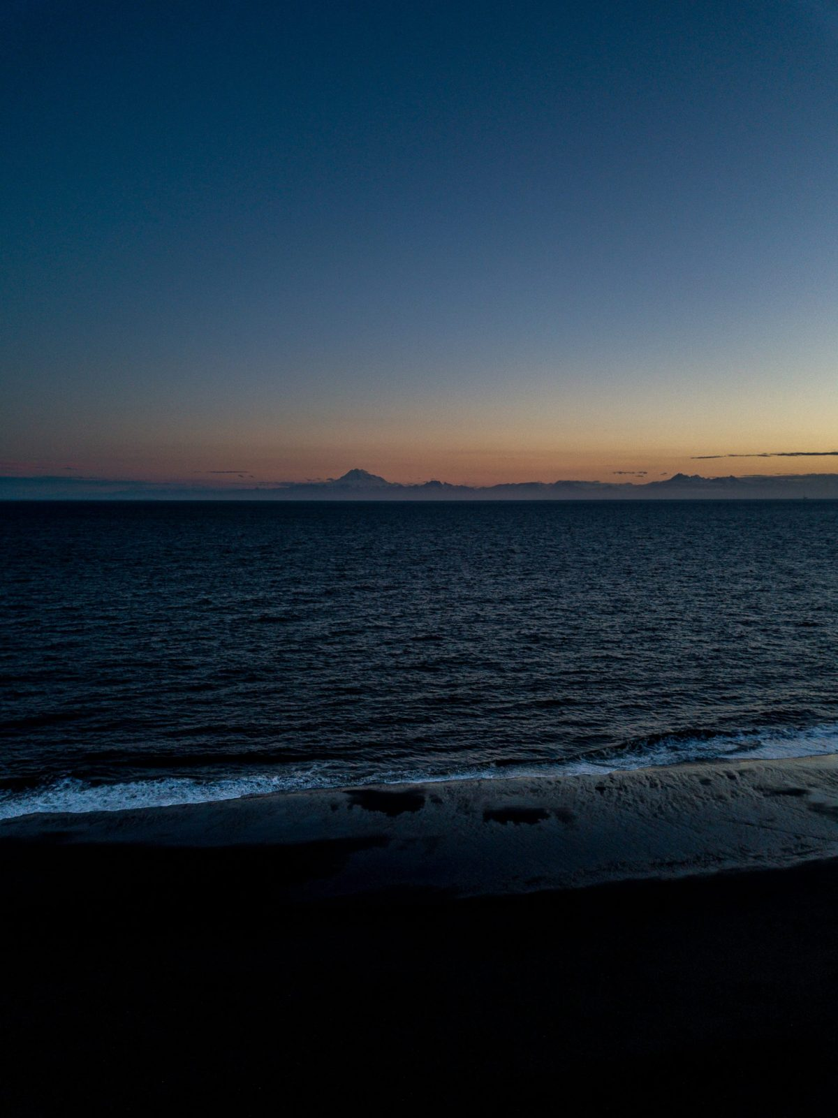 The ocean with mountains in the background, photo taken during the early morning hours.