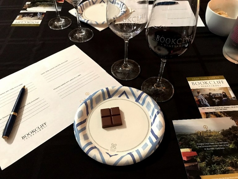 A plate with chocolate, paper for taking notes, and wine glasses at a Moksha Chocolate pairing event.