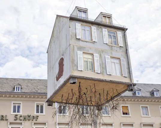 pulled up by the roots, leandro erlich, karlsruhe germany, a city of stars, a city of stars festival, construction art installation, house with roots, house suspended in air, house art exhibit, house art installation