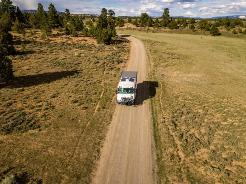 white bus driving down dirt road