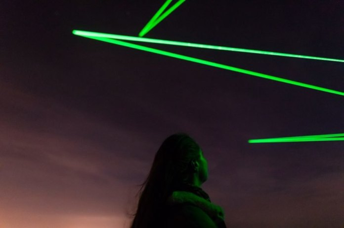 Person looking at green lights in the dark sky above