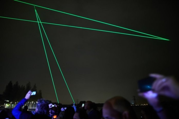Crowd looking up at green laser lights in the cloudy sky