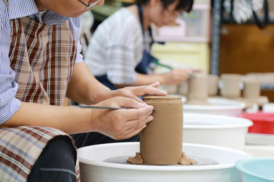 person making a vase on a pottery wheel