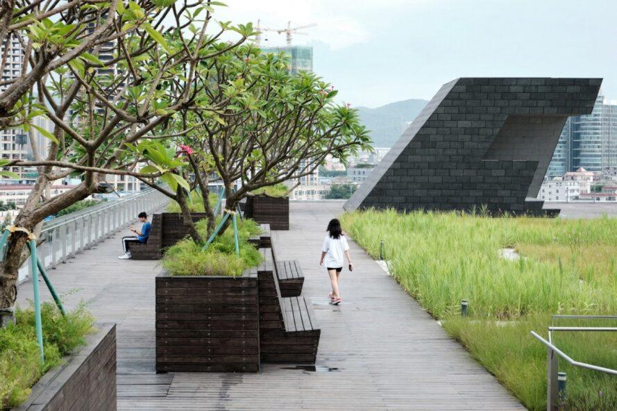 person walking past benches on landscaped rooftop