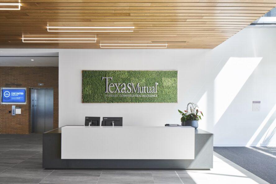 """a lobby with elevators set into a brick wall to the left. to the right are white walls with a green in-set sign reading """"Texas Mutual."""" A dark gray and white desk sits in front of the green sign."""