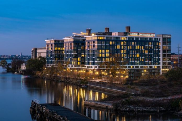 Large glass building near river at dusk