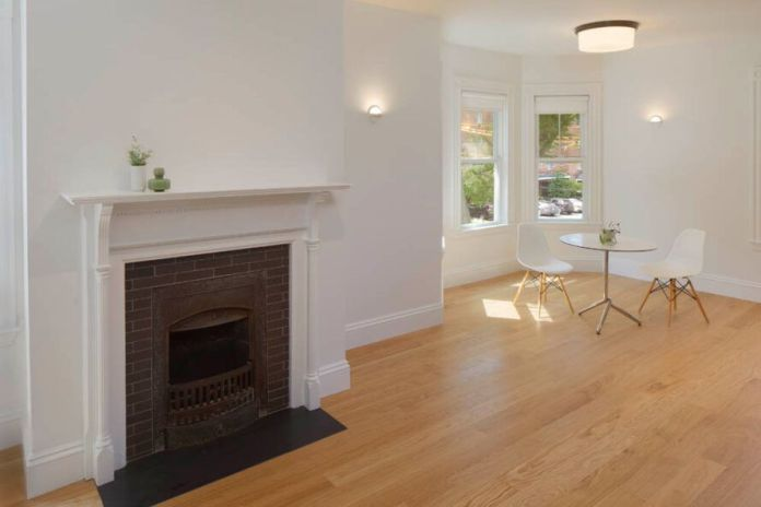 bright white room with wood floors and old fireplace