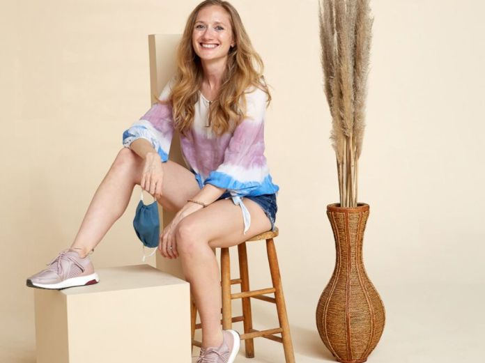 A person sitting on a wood stool next to a brown pot of beige flowers. The person is wearing a white, purple and blue top and shorts.