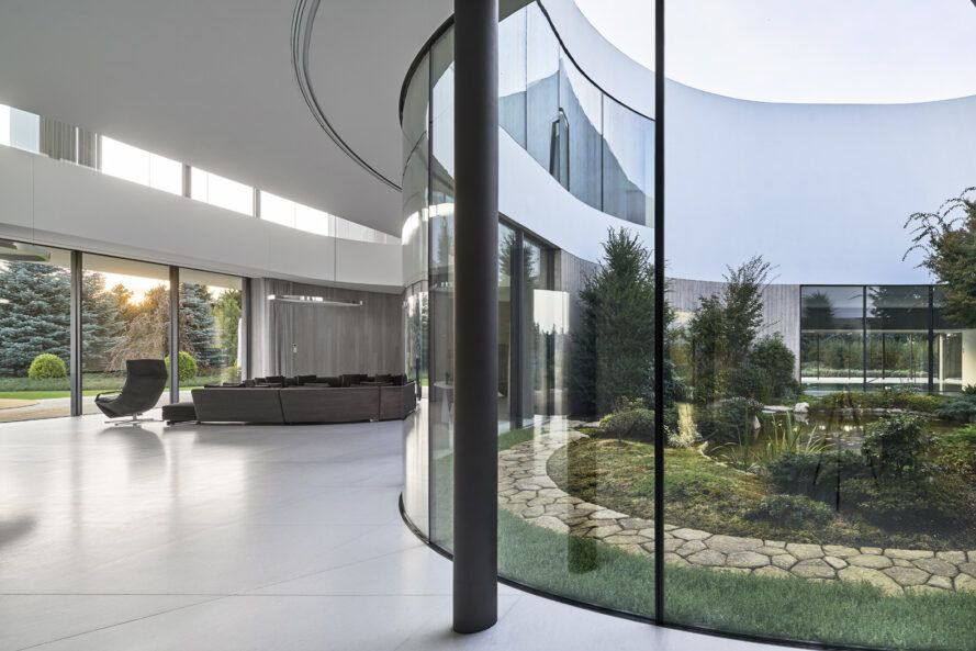 gray living room furniture near curved glass wall