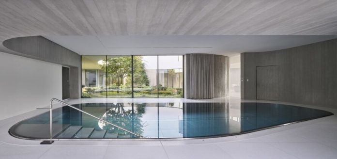 indoor pool in room with glass wall overlooking garden