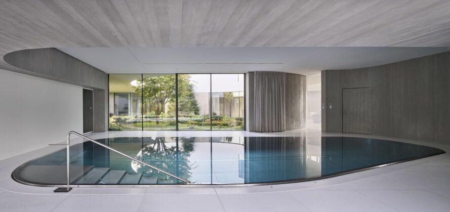 indoor pool in room with glass wall overlooking garden