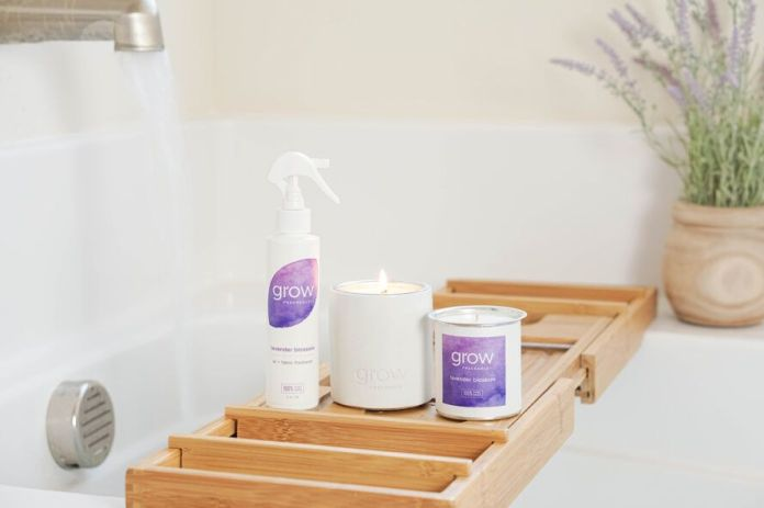 candle and air freshener on wood bath tray
