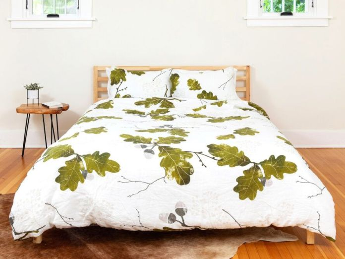 green leaf-print bedspread on wood bed