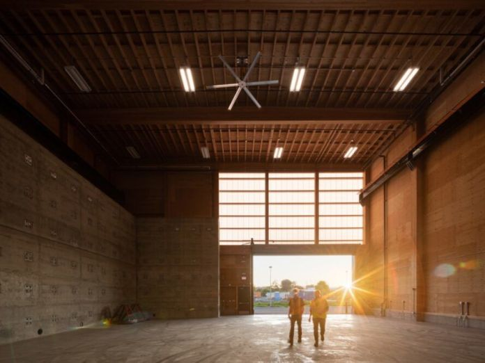 large wood-lined garage room with door opening to reveal the sunset over the horizon