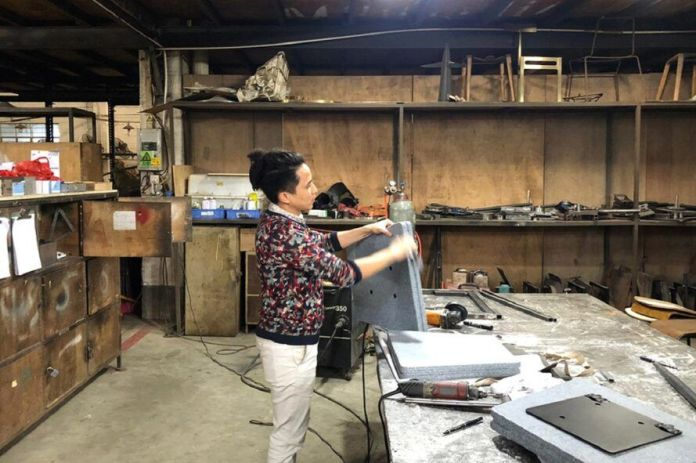 A person working on a bench in a studio setting.