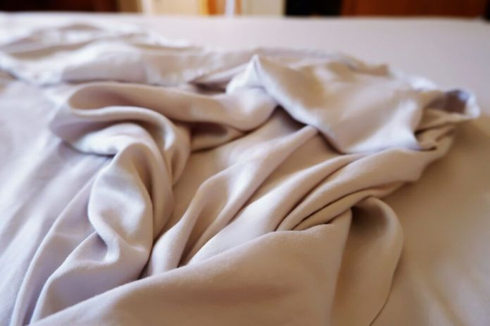 gray sheets on an unmade bed