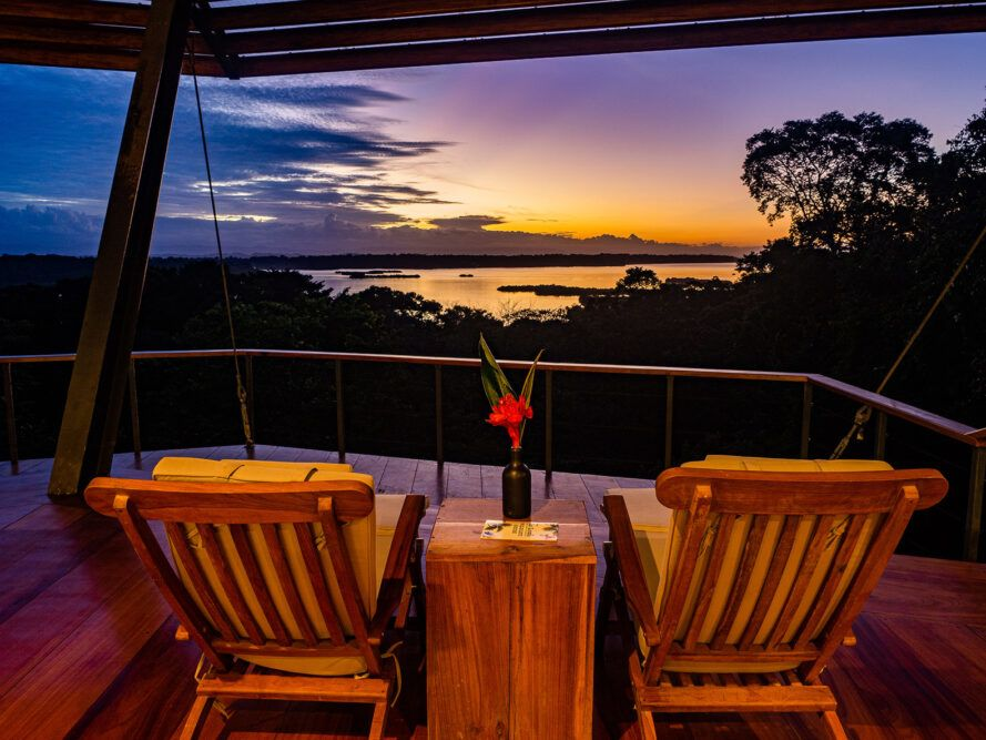 two wood lounge chairs on balcony facing sunset over forest