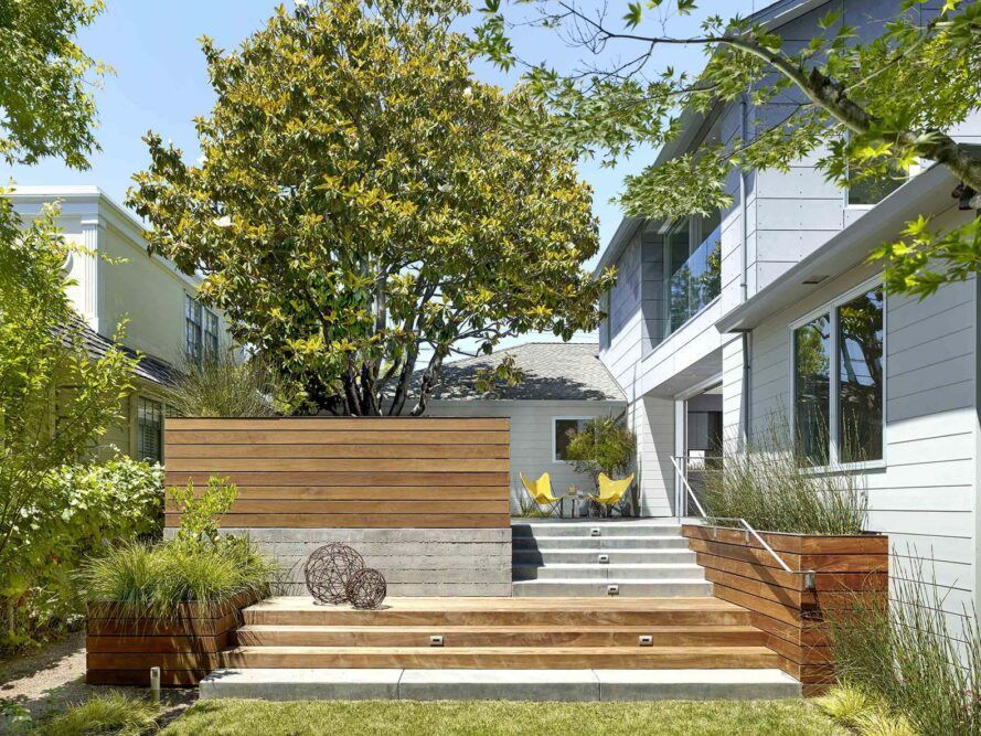 A green yard sits in front of wood and concrete steps that lead up to a house.