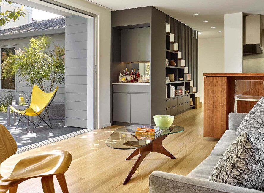 An open living room with wood floors connects to an outdoor deck.