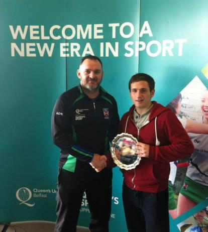 ColáistíInis Eoghain captain Darach O'Connor is presented with the trophy for winning the Queen's Blitz by Aiden O'Rouke