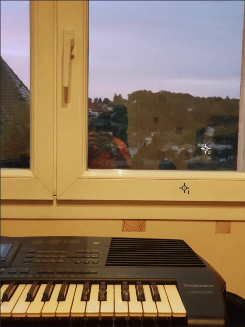 Photo prise en intérieur avec un réglage manuel de la balance des blancs pour neutraliser la dominante de couleur d'une façade d'une maison blanche