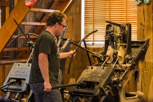 Le sujet de la photographie est l'artisan réalisant la fabrication d'une sabot de bois