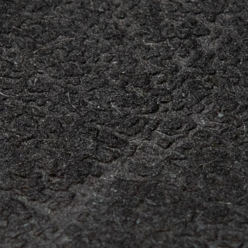 Texture d'une feuille de papier texturée noire en lumière directe