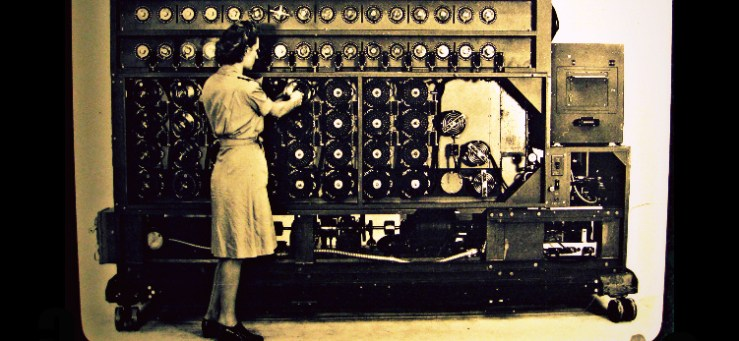 Woman in 1940s garb standing in front of a huge machine with lots of rotors