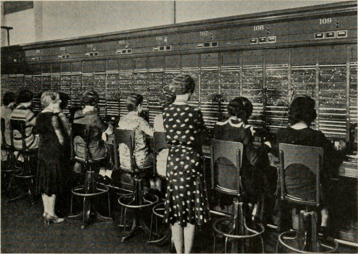 A row of women seated in front of what appears to be an enormous telephone switchboard