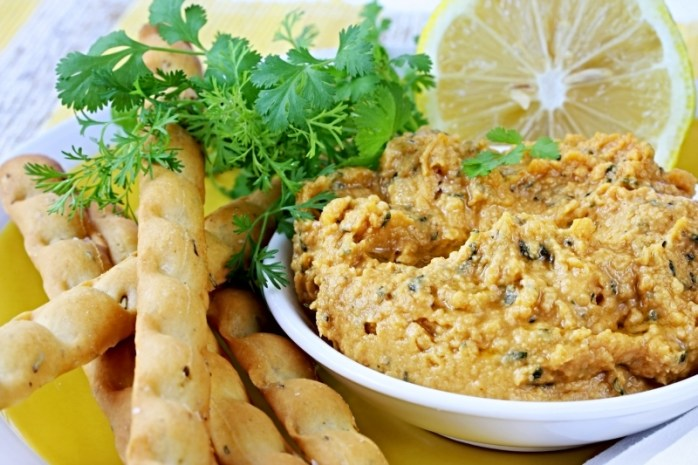 Hummus chickpea dip with lemon and cilantro or coriander.  Served with breadsticks.