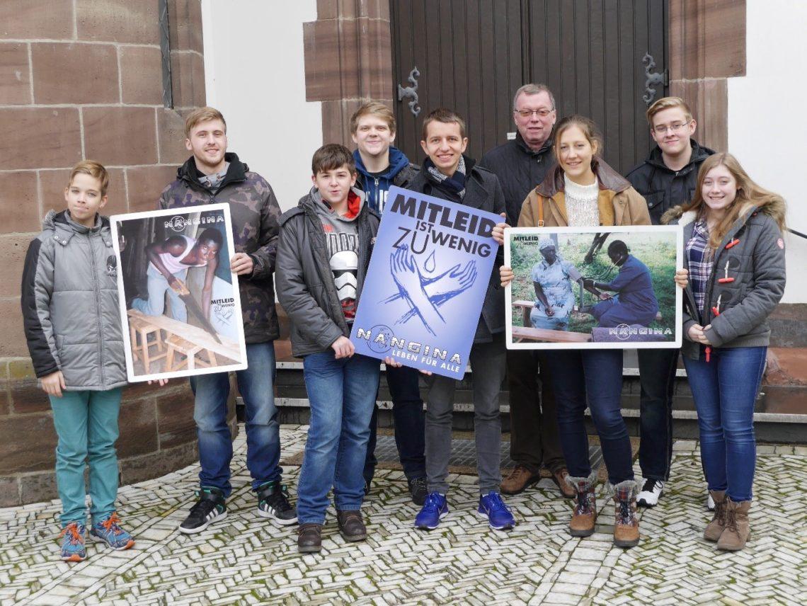 """Acht Jugendliche und ein Erwachsener stehen vor einem Kirchenportal. Sie halten drei große Plakate, auf denen Bilder von Menschen zu sehen sind. Auf einem Plakat sind gekreuzte Hände in Form einer Grafik zu sehen. Das Plakat hat die Überschrift """"Mitleid ist zu wenig""""."""
