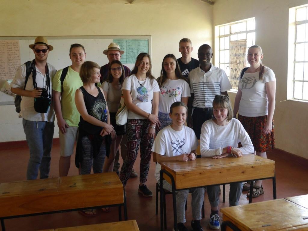 Gemischte Kleingruppe in einem Klassenraum. Alle schauen freundlich und erwartungsvoll. Vorne sind Schulbänke zu sehen, an denen zwei der Besucherinnen sitzen. In der Mitte der Gruppe steht der Gastgeber.