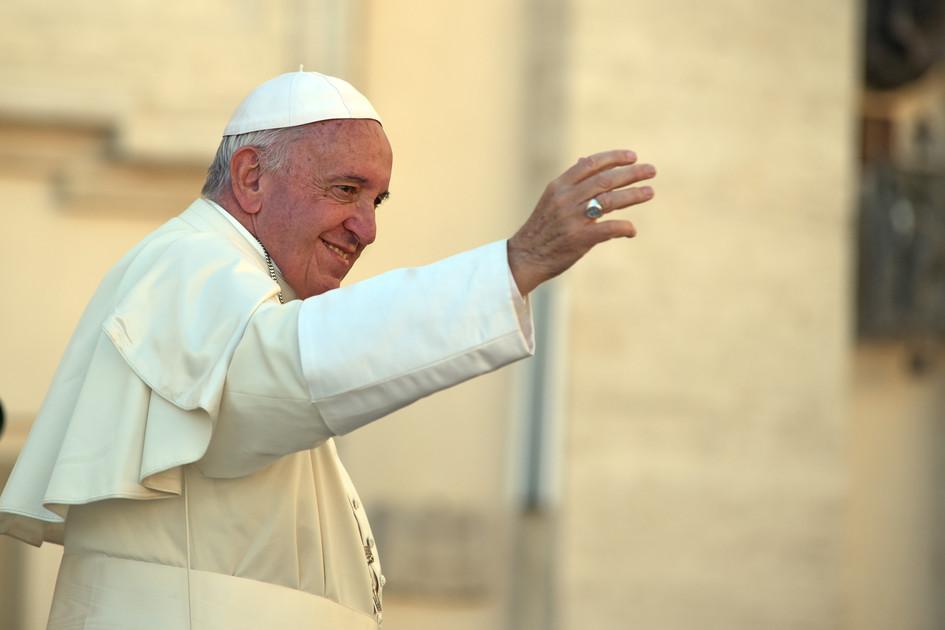 Papst, lächelnd, mit erhobener rechter Hand, an der sein Ring zu sehen ist. Er trägt ein weißes Gewand und eine weiße Kappe.